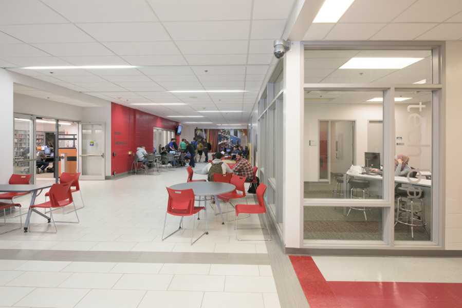 White corridor with red decal, informal student lounge seating, with glazed resource centre on left and tech bar on right