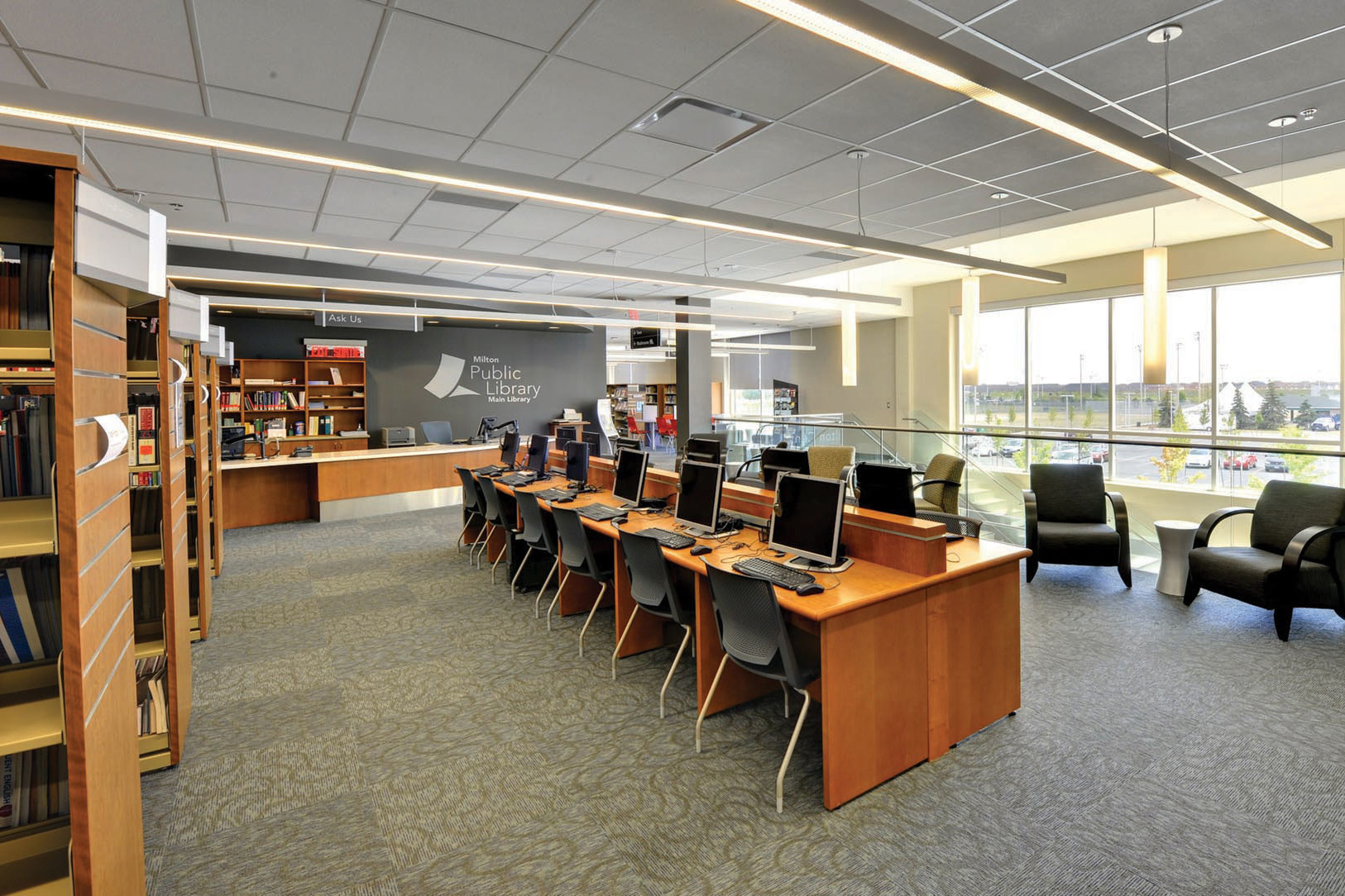 Resource centre with computer work stations, lounge seating, wood bookshelves and white pendant lighting