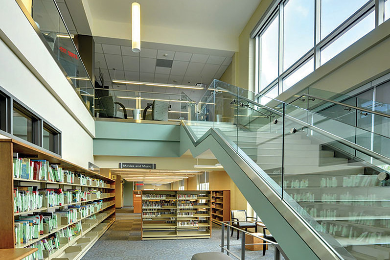 Wood bookshelves on ground floor with open staircase with glass guard rail leading to second floor