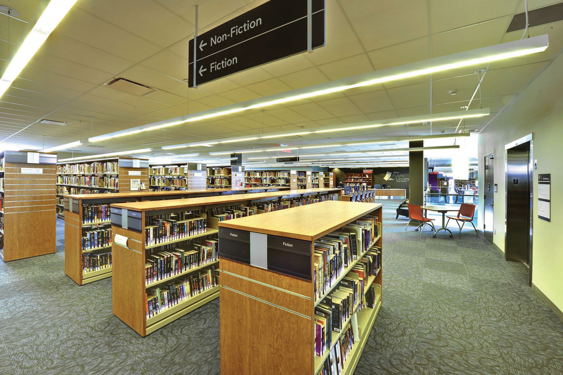 Rows of wood bookshelves with overhead signage