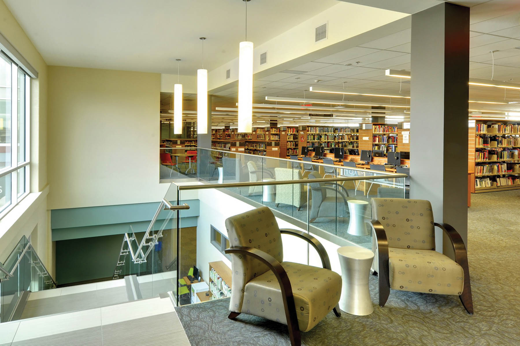 Lounge seating along top of double height staircase with large windows, glass guard rail and white pendant lighting and wood book shelves in rows