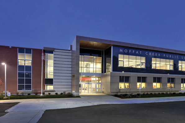 Illuminated two storey school with double height glazed front entrance lobby at dusk