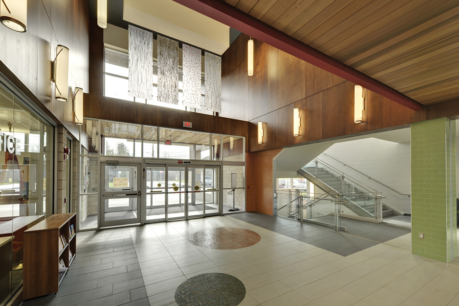 Glazed double height front entrance lobby with wood walls and ceiling and exposed staircase with glass rail guards
