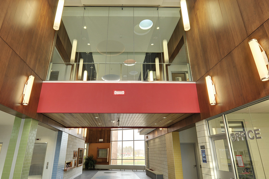 Double height front entrance lobby with glazed second storey corridor, wood panel walls and white pendant lighting