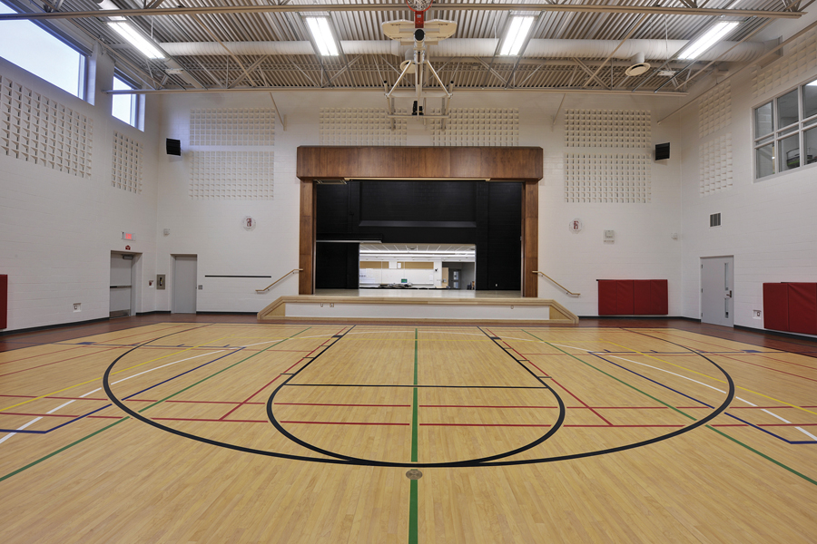 Gymnasium with white walls, exposed beam ceiling, retractable basketball nets, stage, and clerestory windows