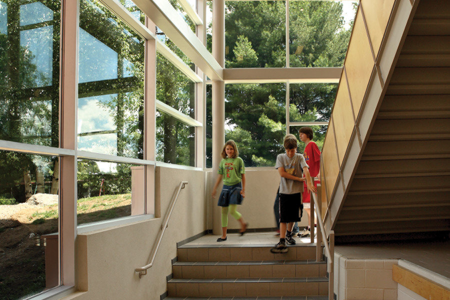 Students walking down double height glazed staircase with built in wood bench and views of trees