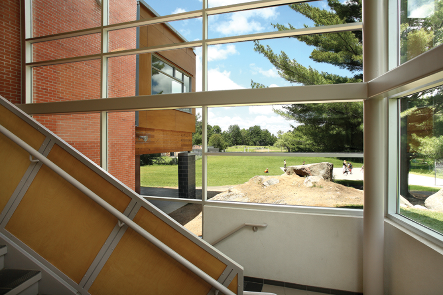 View from large steel framed windows of double height staircase to large rocks, trees and green field with students playing