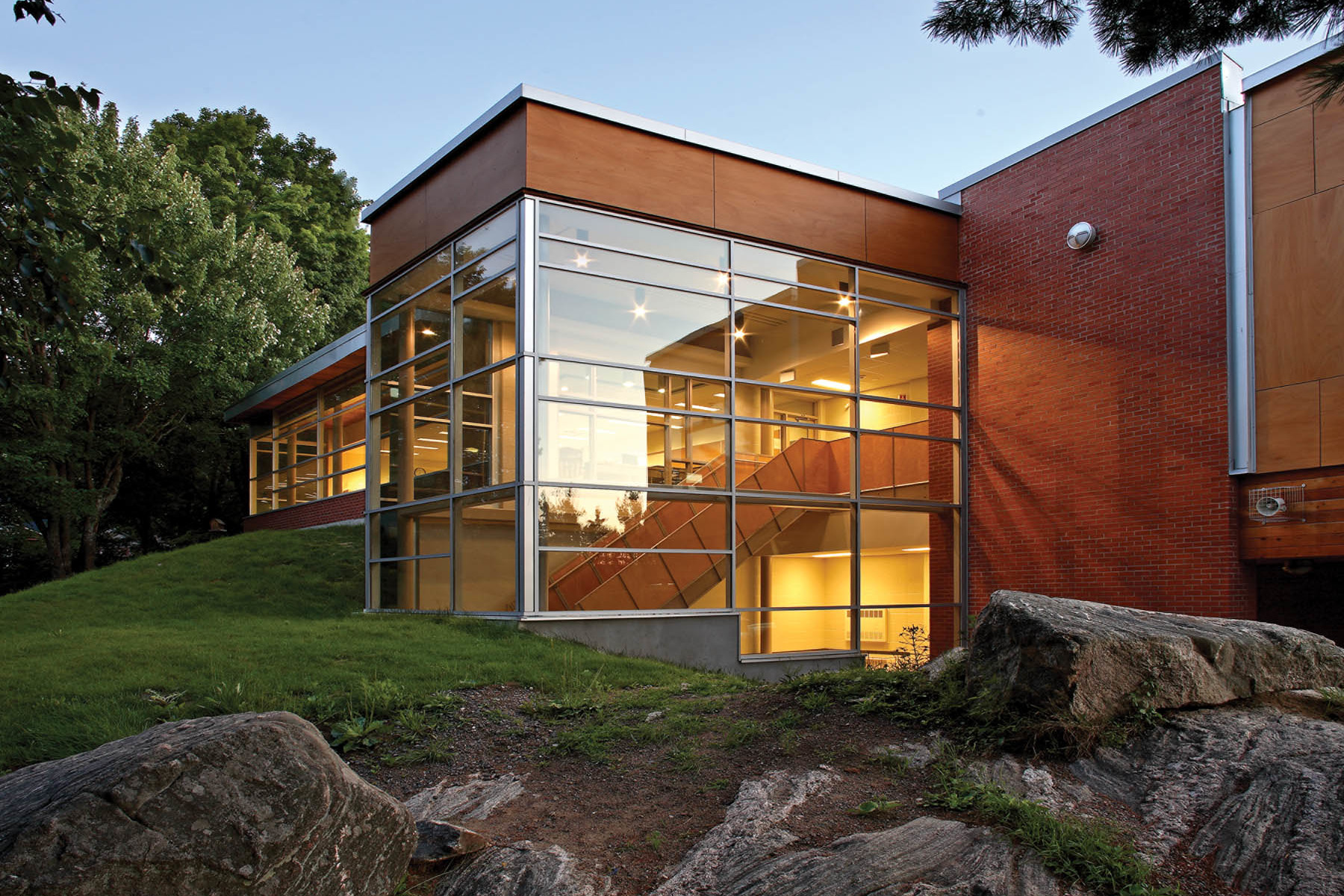 Illuminated glazed double height staircase and red brick façade nestled in green hill with trees and large rocks at dusk