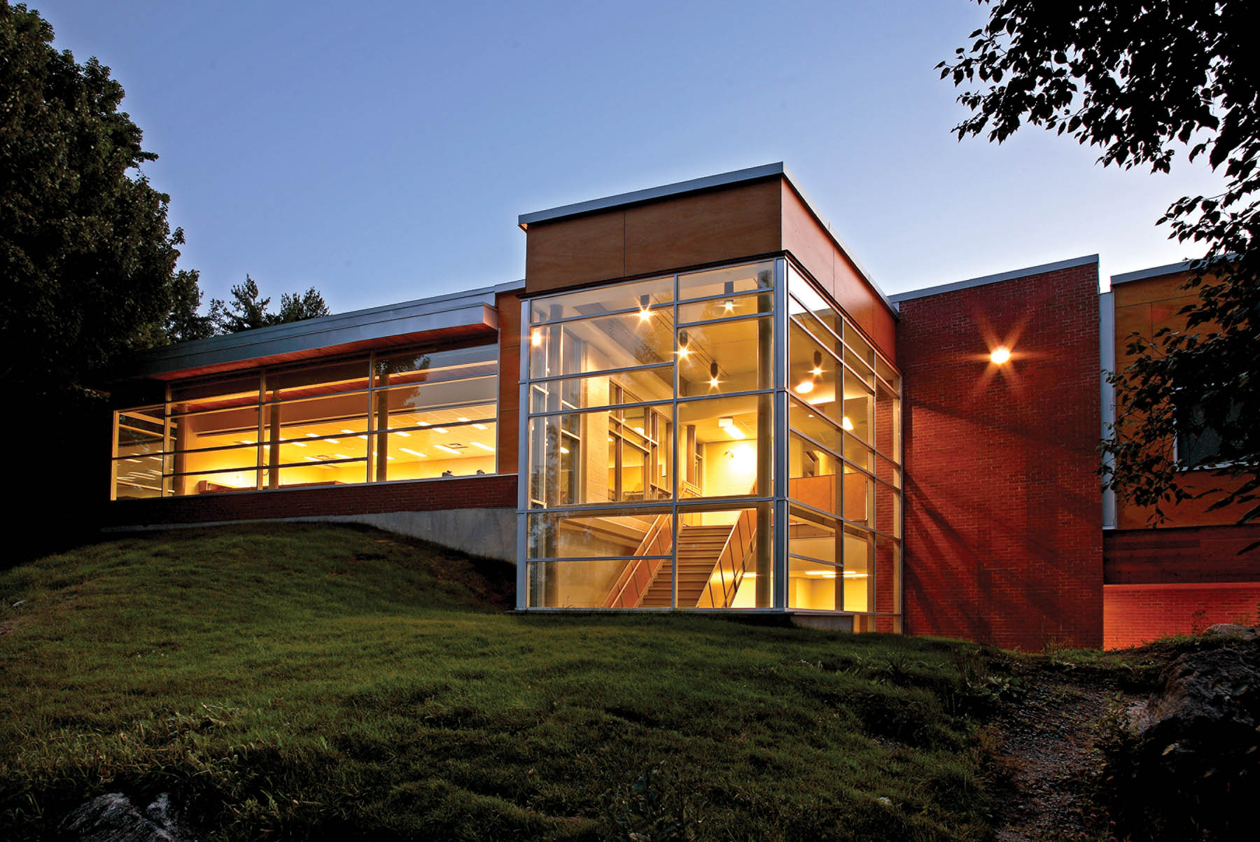 Illuminated glazed double height staircase and red brick façade nestled in green hill at dusk