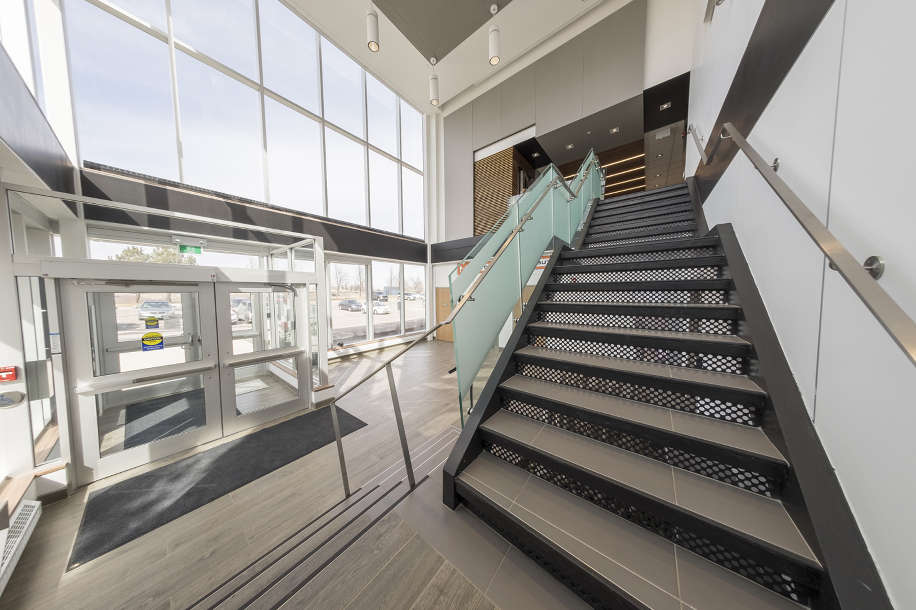 View of double height front entrance lobby with white pendant lighting from open steel staircase with frosted glass guard rail