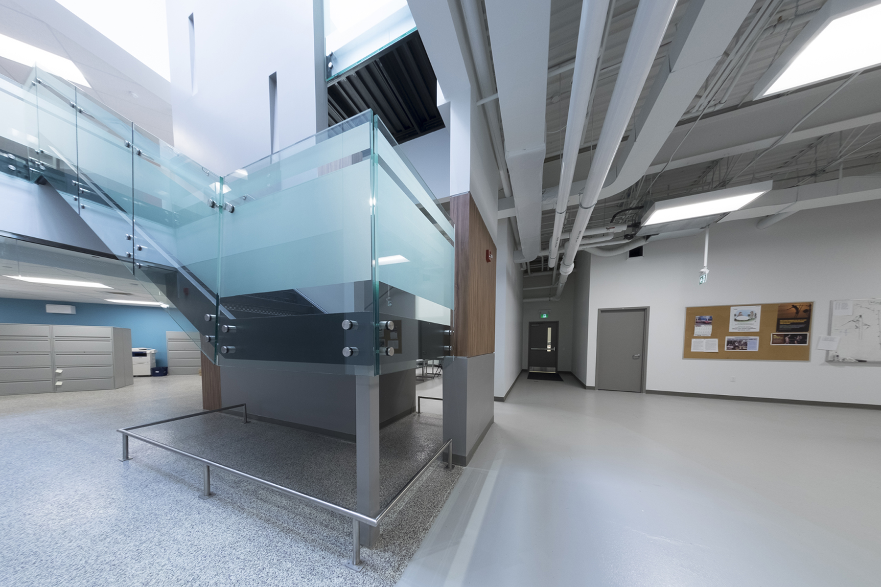 Entrance lobby with exposed staircase with glass guard rail with fastening detail