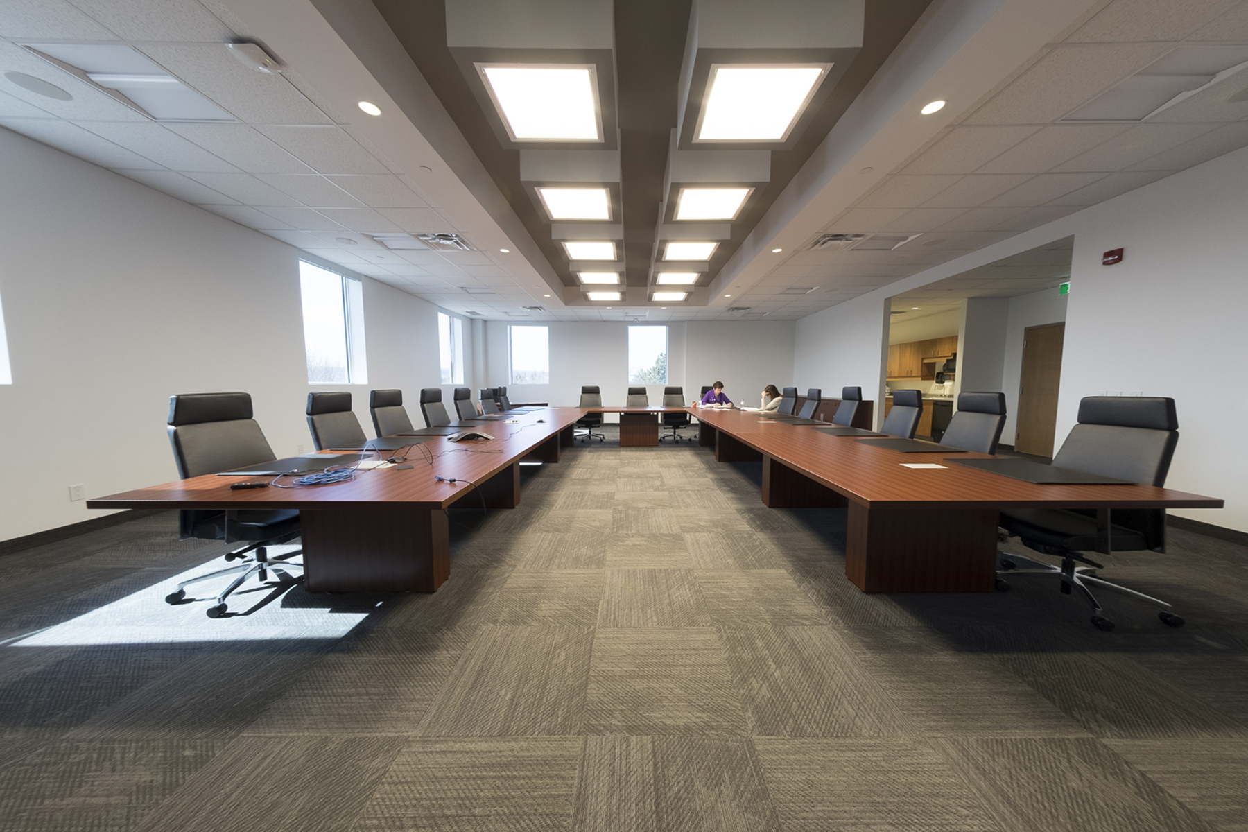 Boardroom with large U shaped wooden table and paneled light boxes on ceiling
