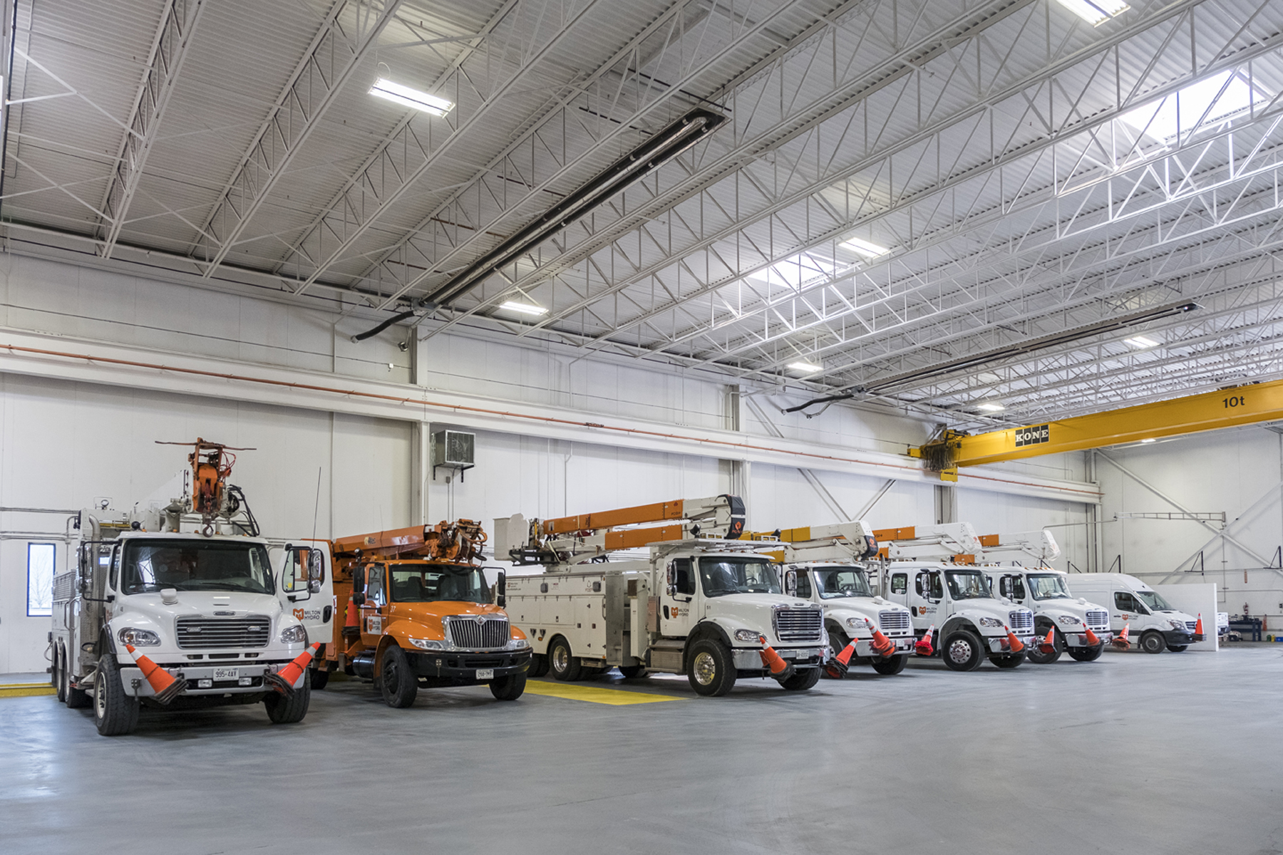 Large white garage space housing maintenance trucks and vans with exposed yellow structural beam and white structural ceiling