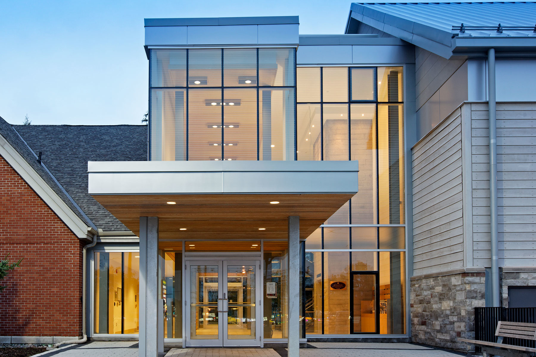 Illuminated glazed front entrance with wood and steel cantilever roof at dusk
