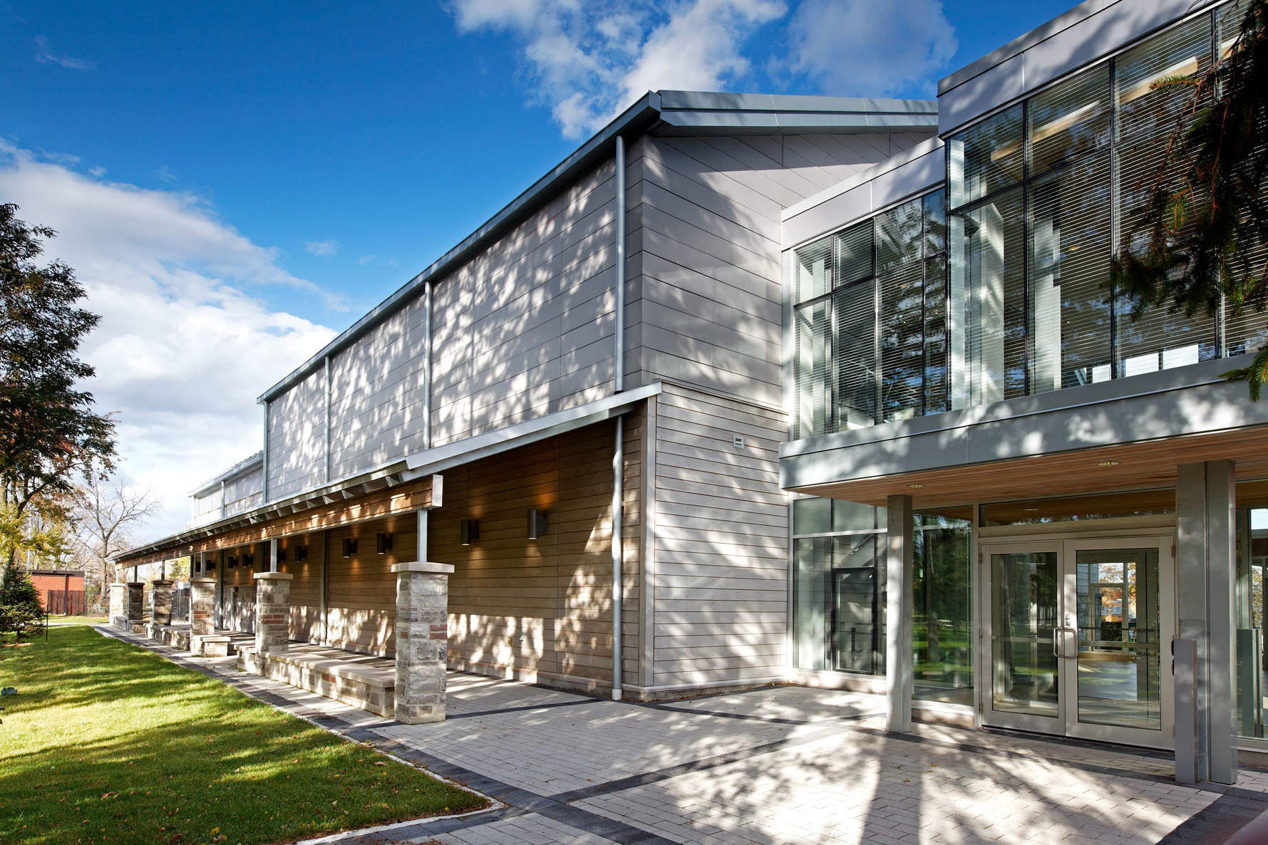 Glazed front entrance with wood and steel cantilever roof and lit colonnade running length of building with trees on a sunny day
