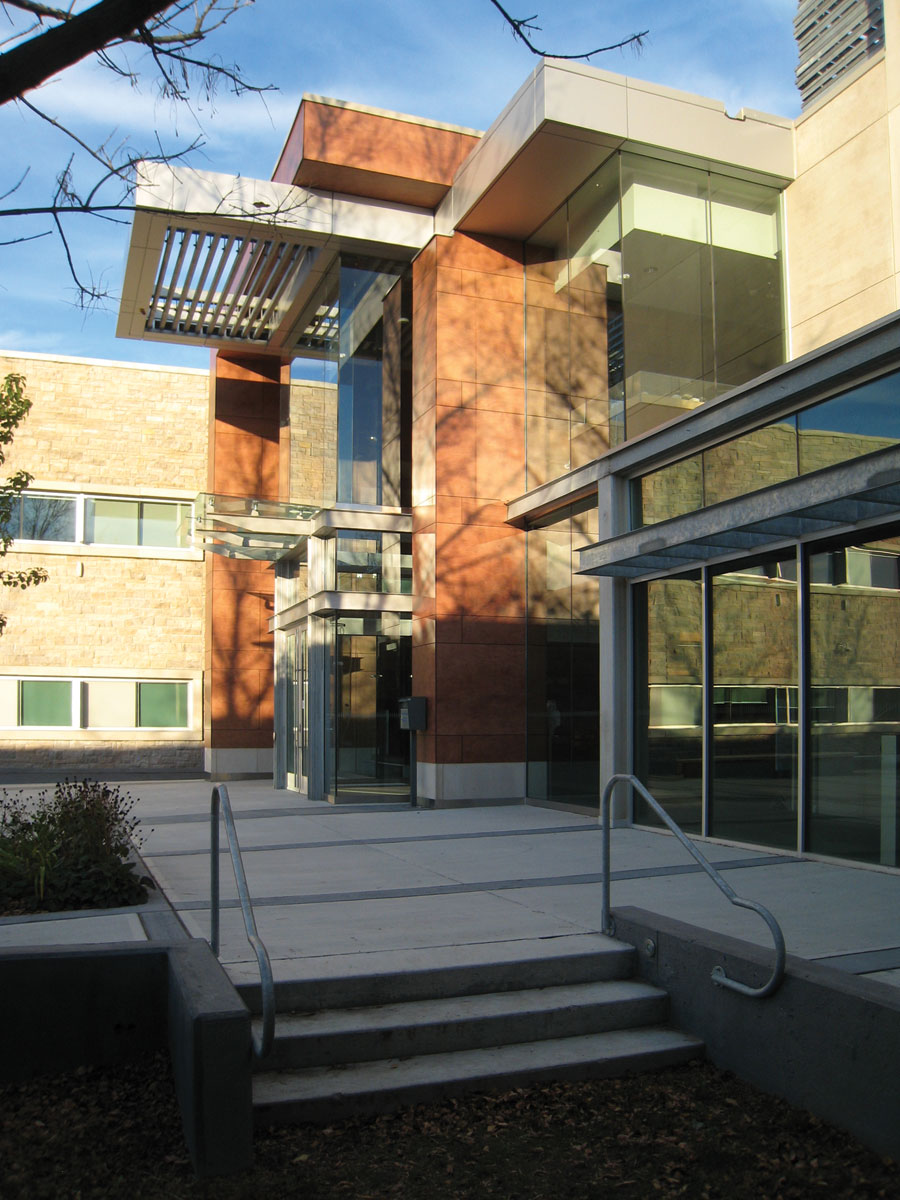 Steps leading to new double height front entrance lobby with cantilever steel trellis roof