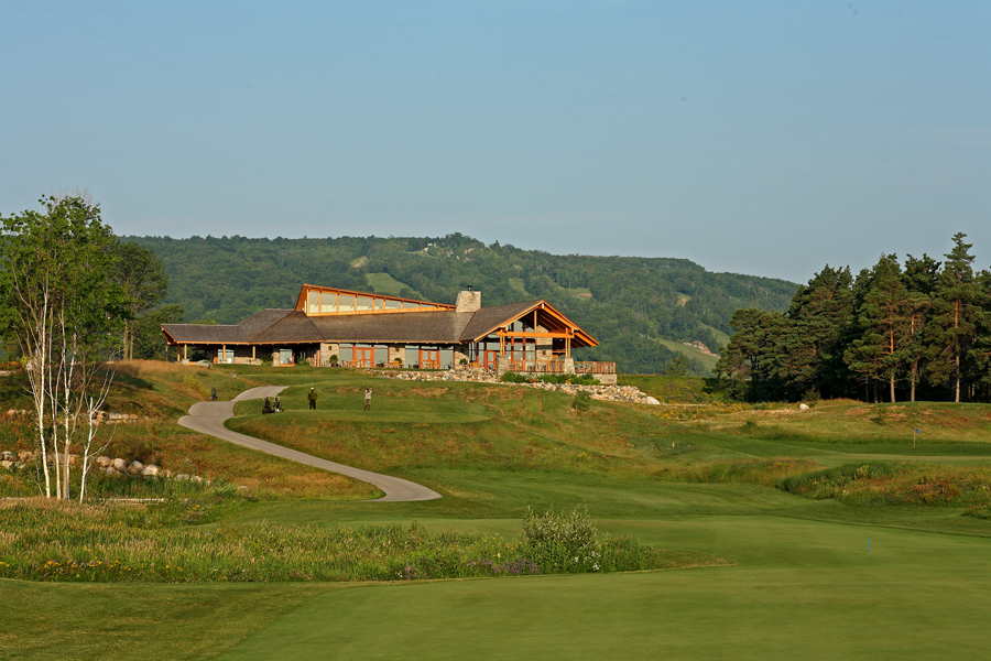 Clubhouse with slanted wood roof, clerestory windows, exposed wood rafters and wood columns nestled in green hills and trees
