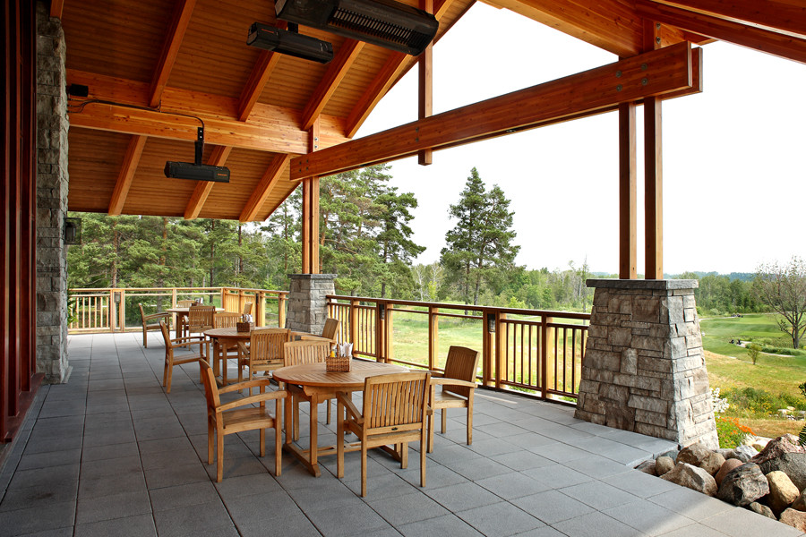 Covered porch with exposed wood rafters and wood columns with cut stone bases looking out to golf course and trees