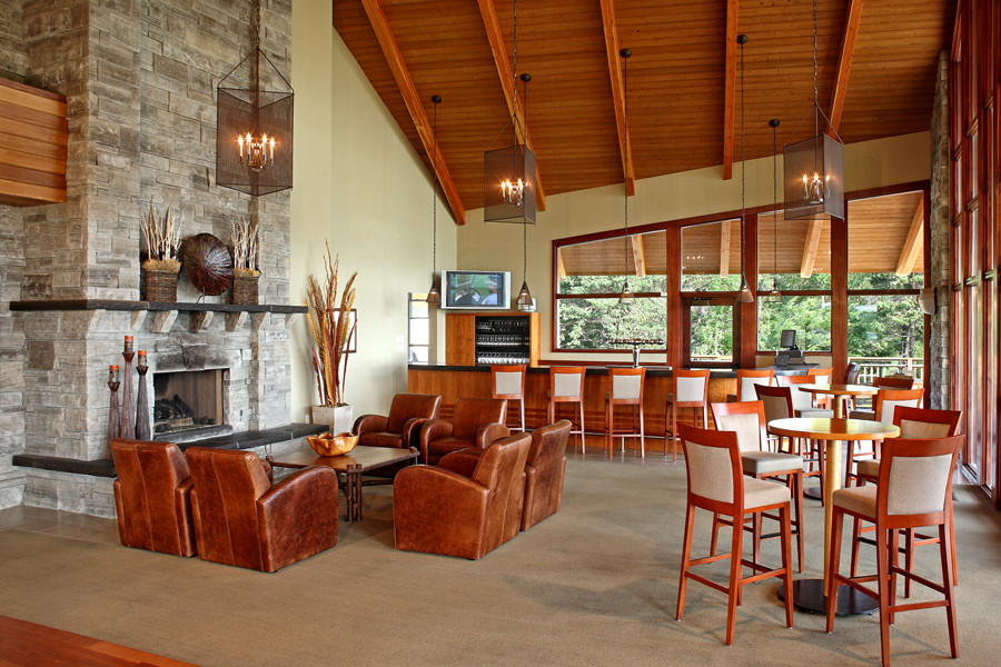 Tan leather armchairs around stone fireplace feature with bistro tables and bar with wood rafter ceiling and black iron chandeliers