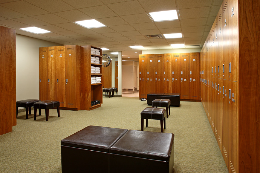 Locker room with large wood lockers and dark brown leather stools and bench seating