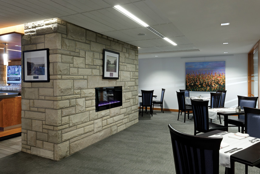 Stone wall fireplace feature with bar on left and table and chair seating on right
