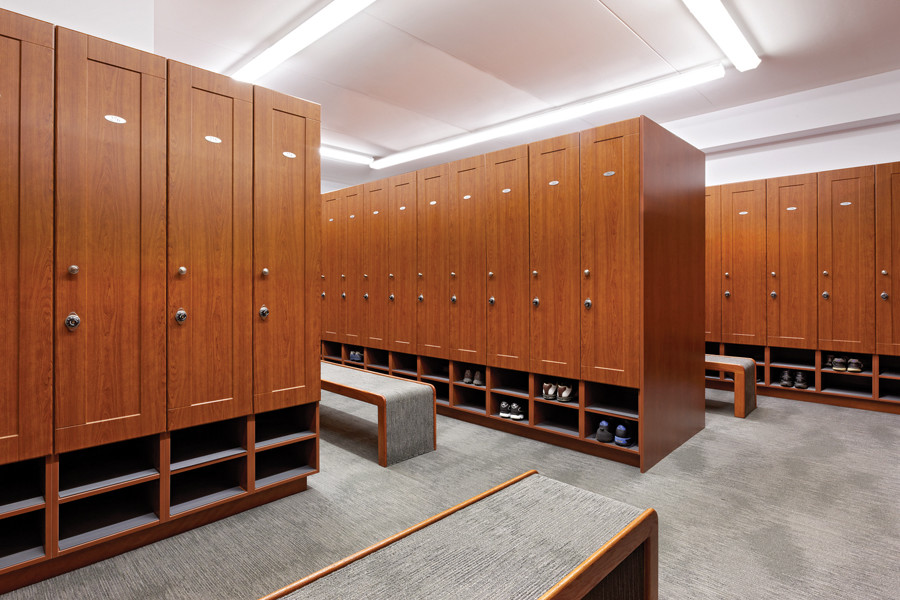 Locker room with large wood lockers and grey carpet and benches