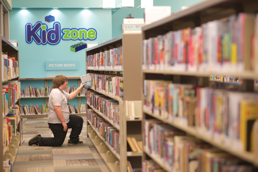 Child taking a book off bookshelf in Kid Zone with lettering and lego logo on blue feature wall