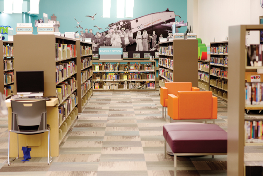 Bookshelves with historic photo mural on wall and orange and purple chairs