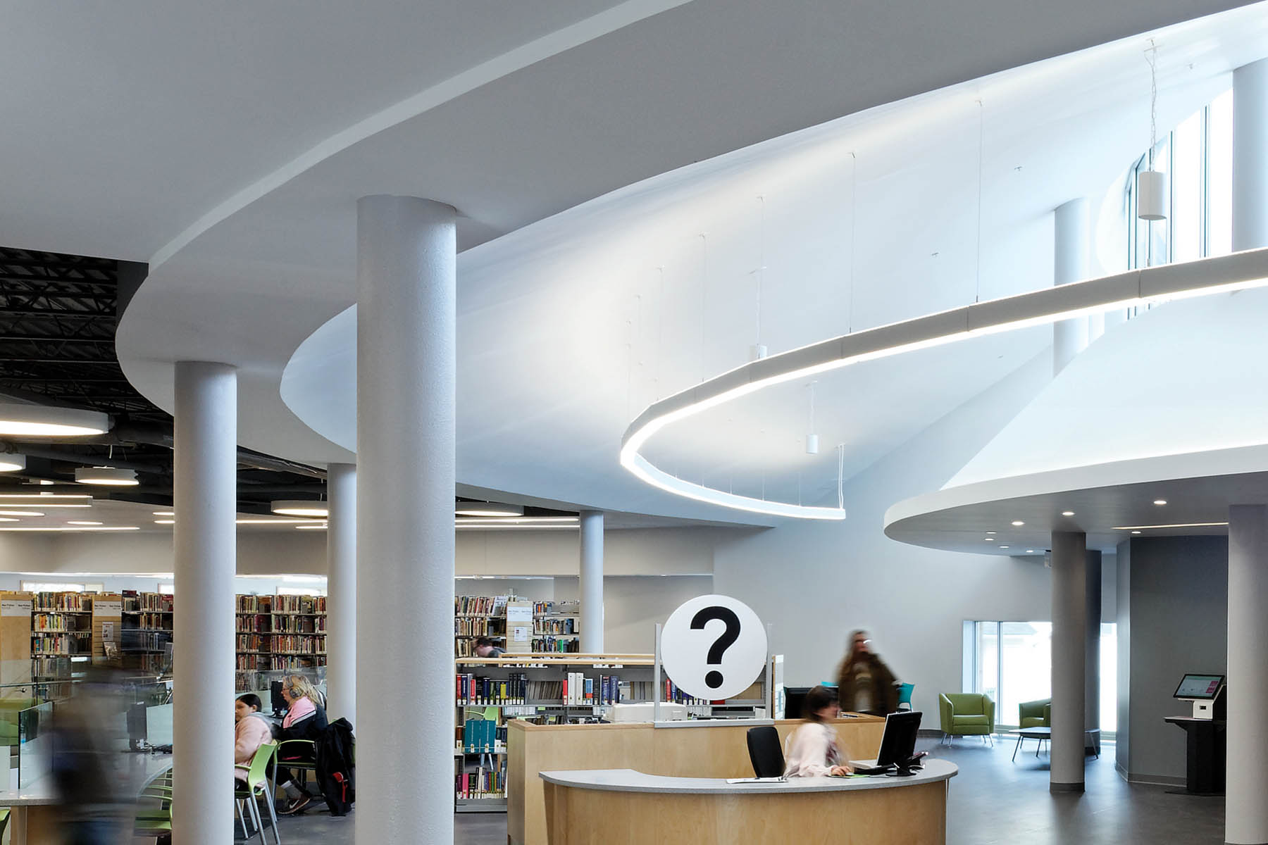 Information desk with large question mark signage, white columns, bookshelves and tiered ceiling with clerestory windows