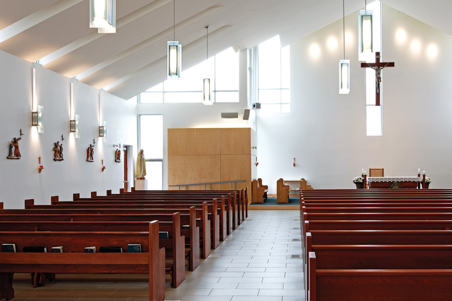 Front of Sanctuary with cross feature, wood pews, slit and clerestory windows, and custom steel and glass pendant lighting