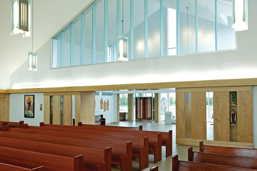 Back of Sanctuary with wood pews, large triangular clerestory window and wood panel doors leading to foyer