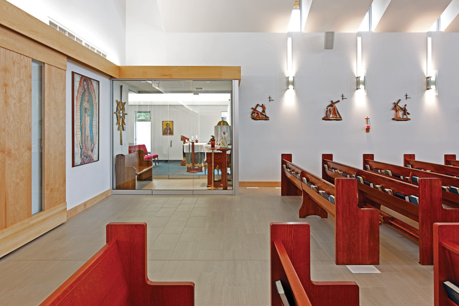 Back of Sanctuary with wood pews, slit windows and steel and glass sconces and wood carvings