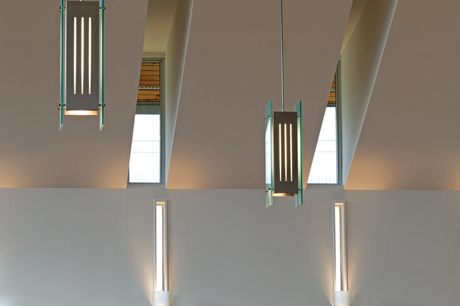 Slit windows with custom steel and glass pendant lighting and sconces, and wood carvings on white walls