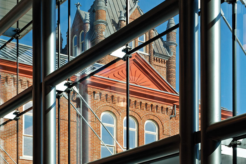 Detail of glass facade structural fastening of addition looking through to original red brick Victoria school house in background