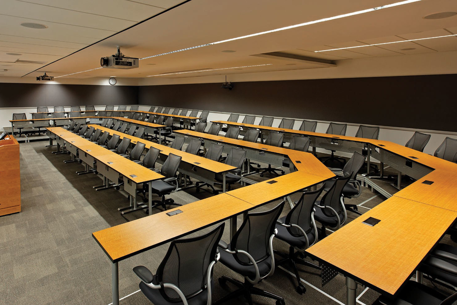 Lecture hall with four tier seating with black mesh back chairs, podium, overhead projector