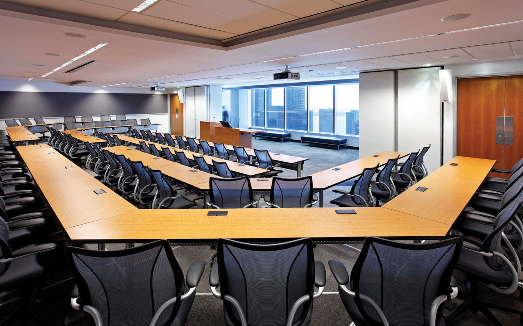 Lecture hall with four tier seating with black mesh back chairs, podium, overhead projector and perimeter windows with views of lake and city
