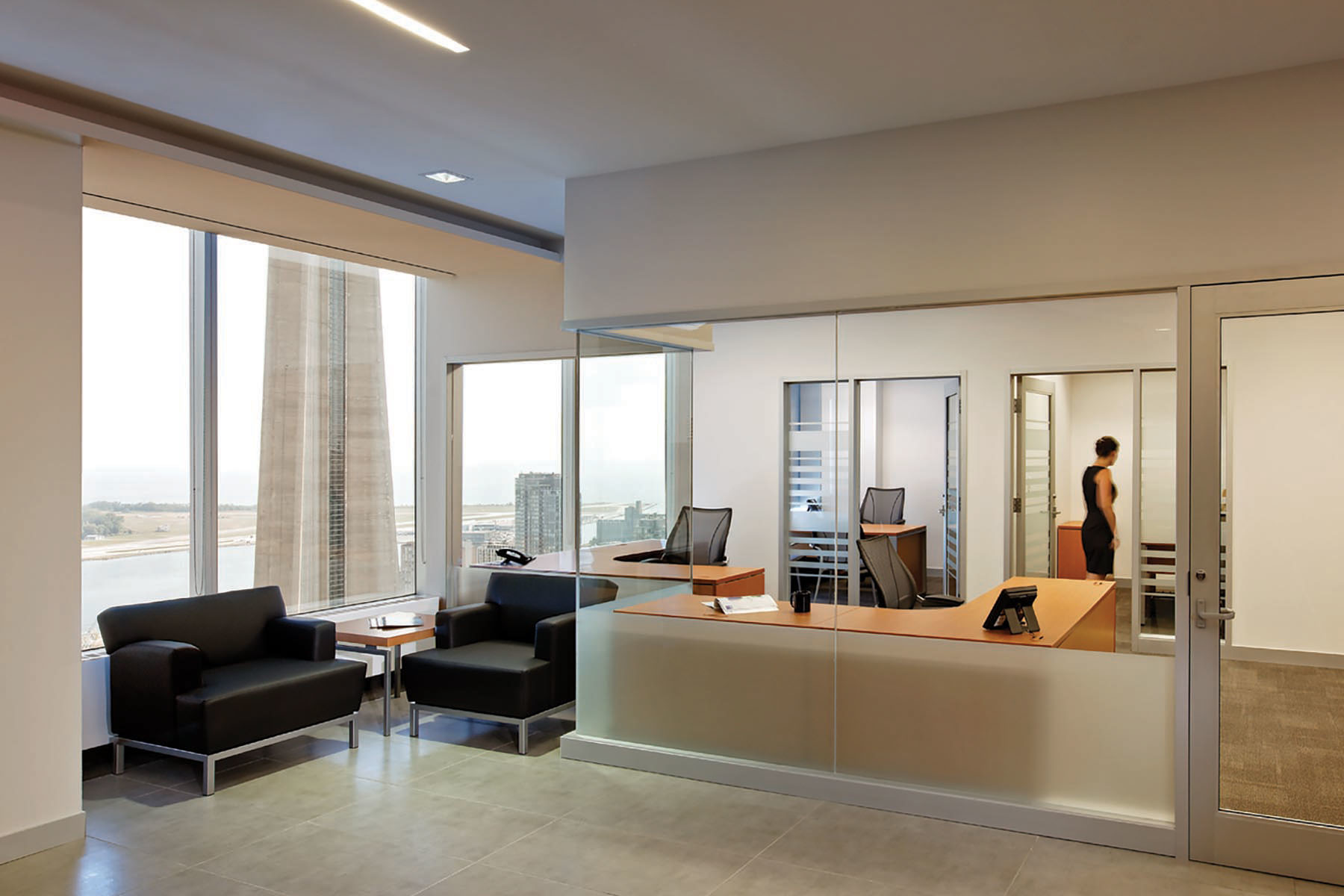 Corner lounge seating with views of Lake Ontario and CN Towner with glazed reception area and semi private offices