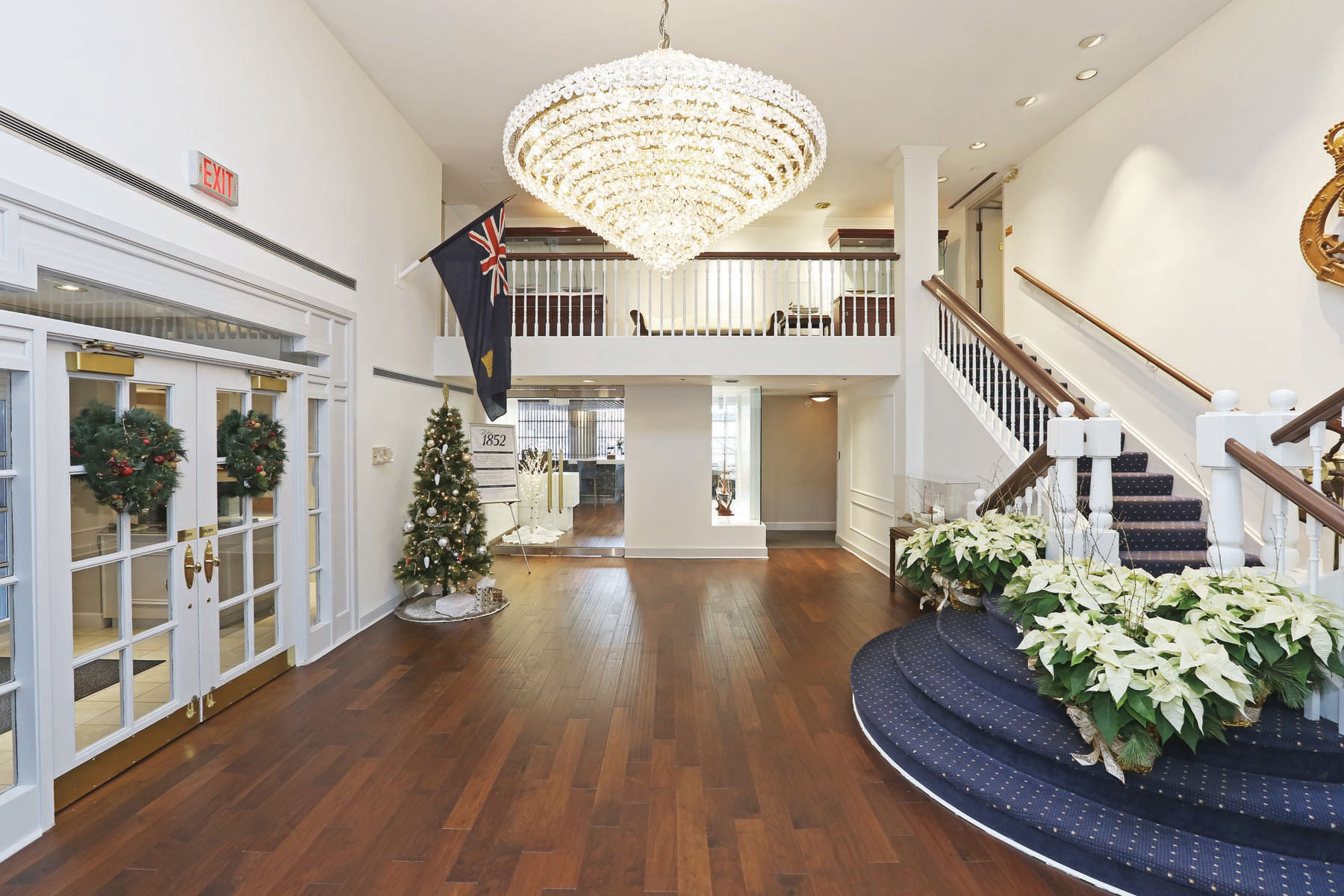 Foyer with large crystal chandelier, French doors on left and blue carpeted wood staircase on right leading to open second storey