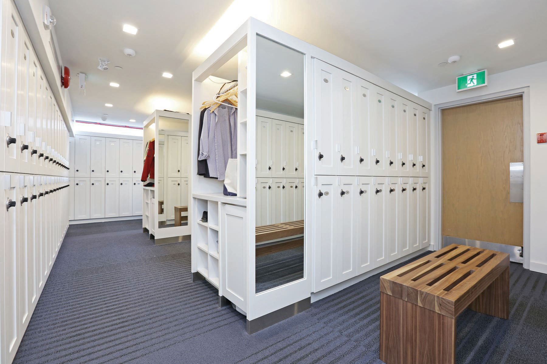 Large white wood lockers with full length mirror, wardrobe space and wood bench
