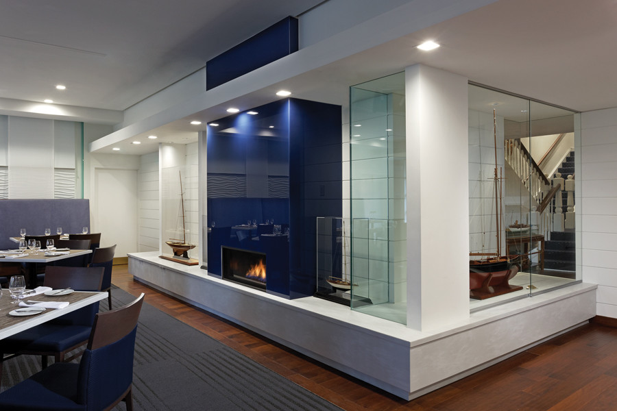 Blue fireplace feature in dining room with dining tables and blue banquet and glazed curtain wall looking through to foyer