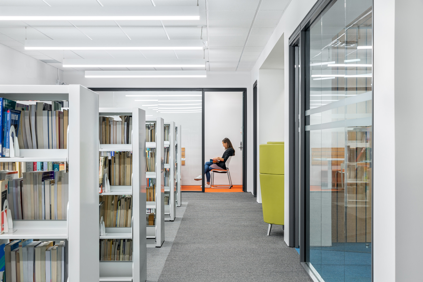 Student reading in private glazed study room at end of corridor with white bookshelves on left and glazed meeting room on right
