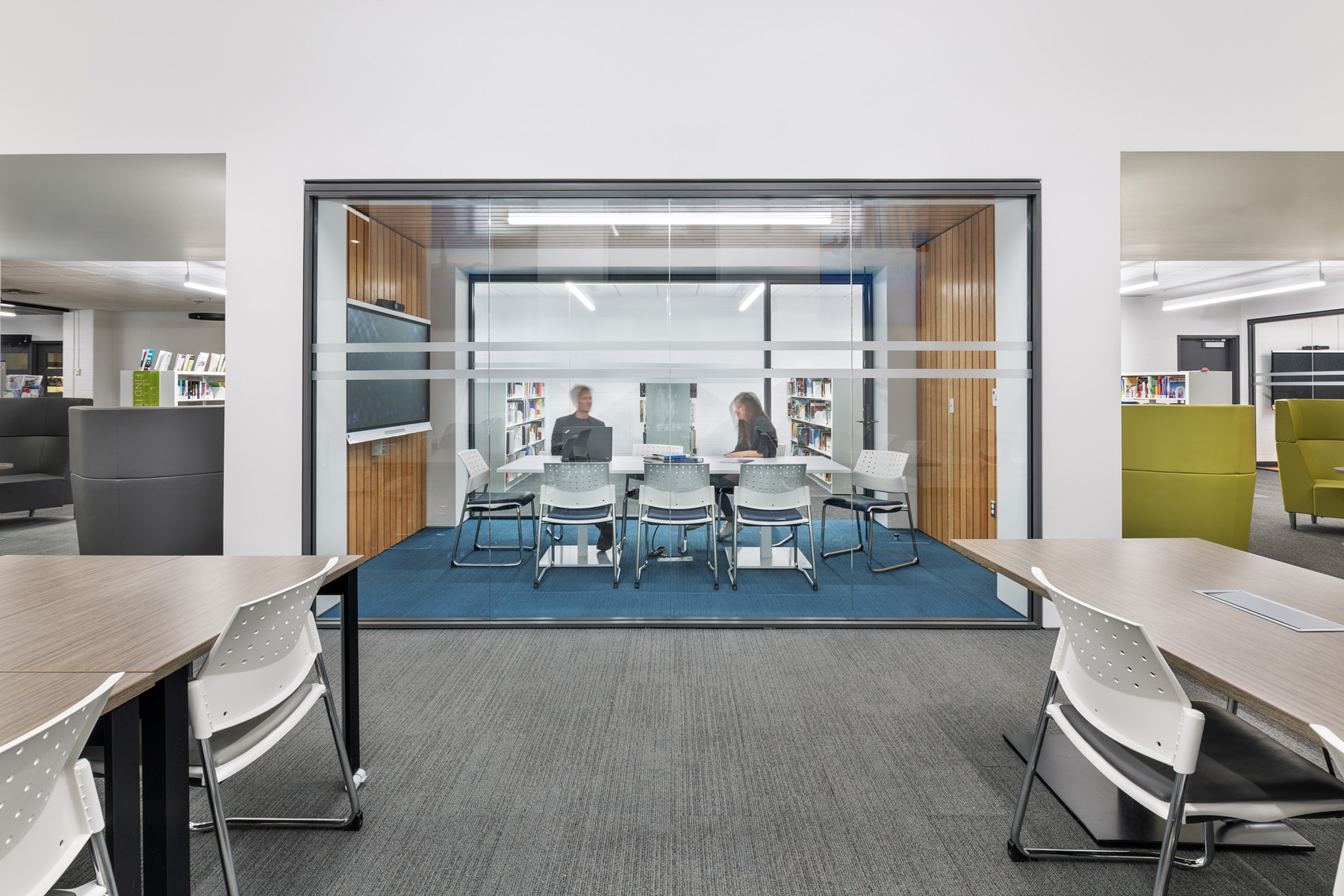 Two students in central glazed meeting room with blue carpet, white chairs, wood plank floor and ceiling feature and tv screen