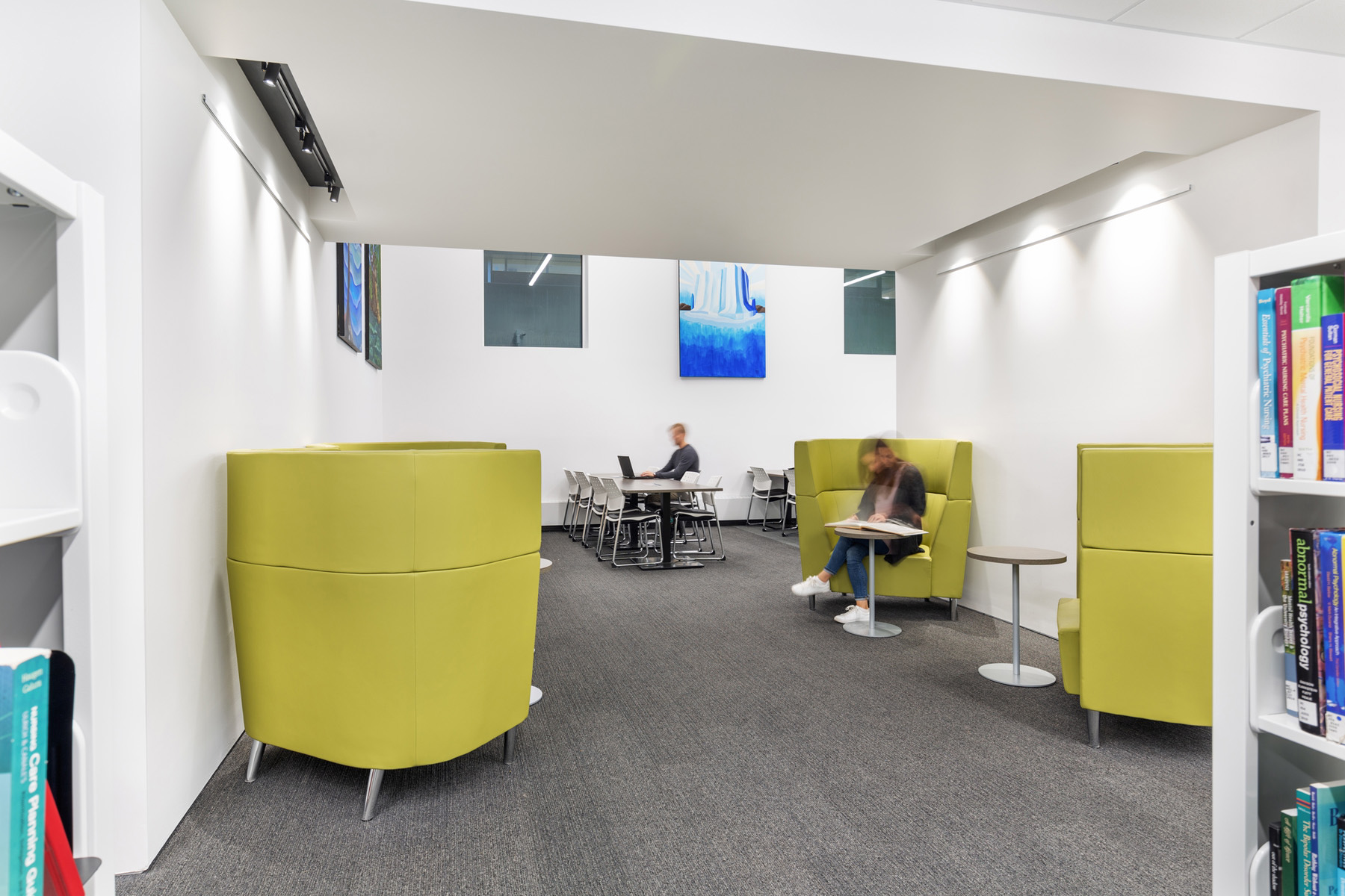 Student studying on high back lime green armchair with group study tables in background