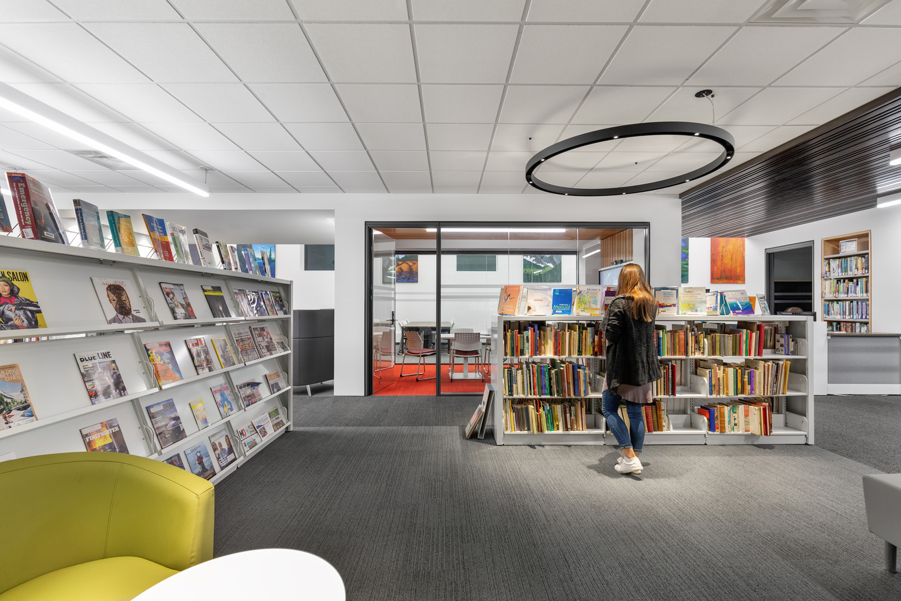 Student browsing bookshelves with magazine rack and green lounge chair on left with glazed meeting room in background