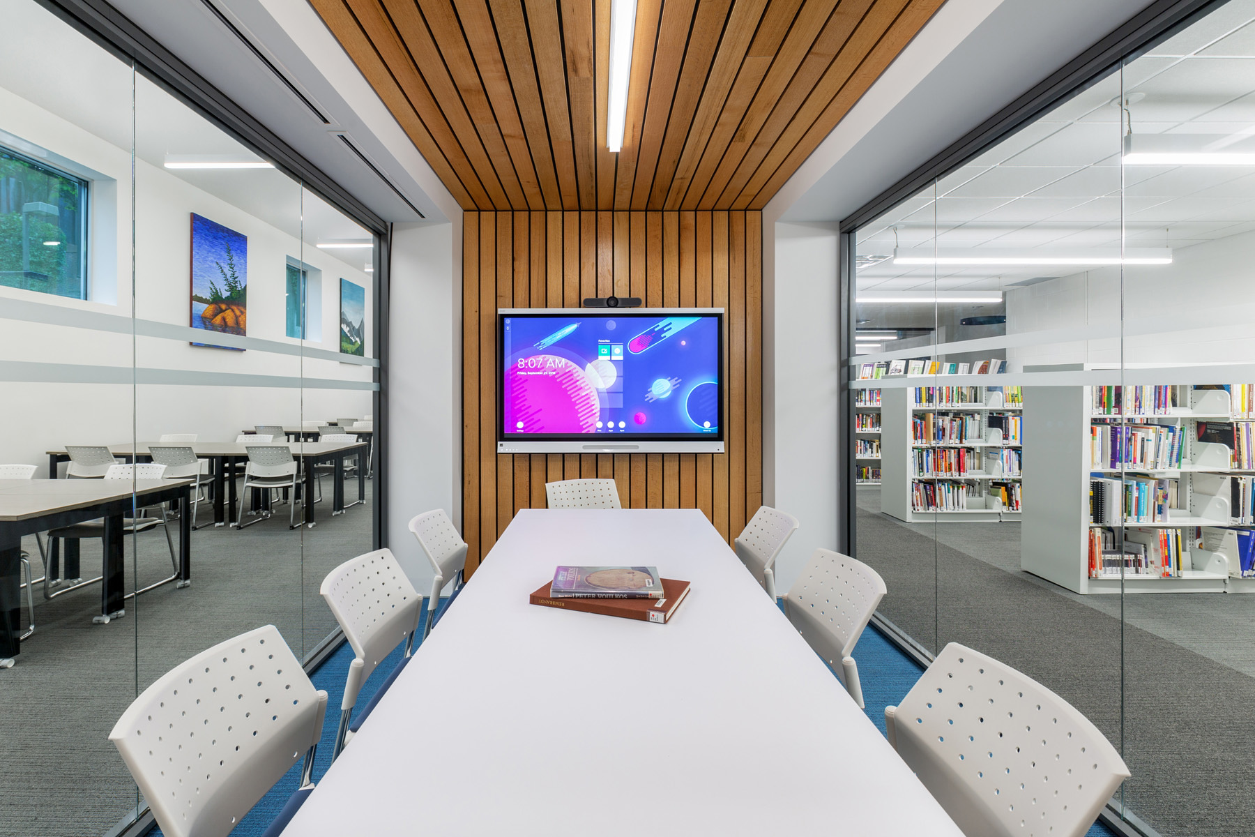 Glazed meeting room with white table and chairs, wood plank floor and ceiling feature and tv screen, with bookshelves on right
