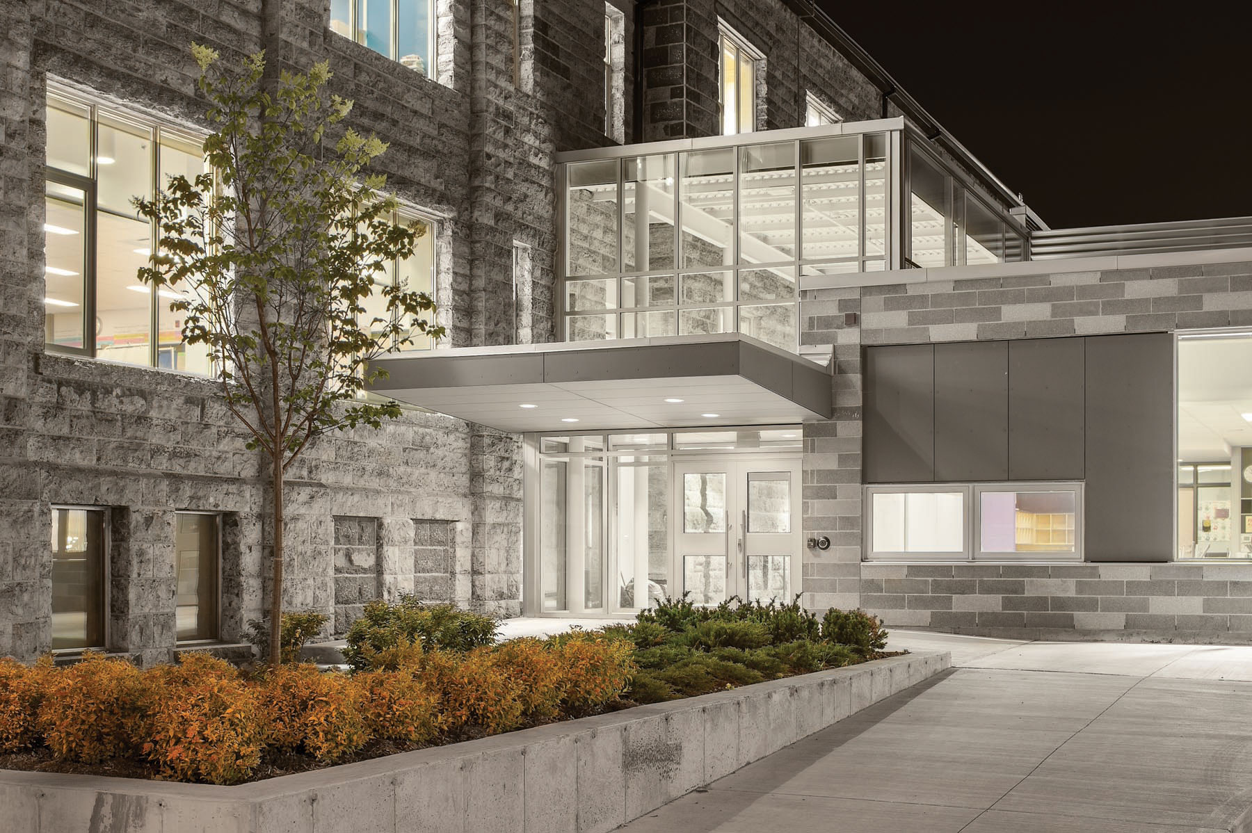 Night view of illuminated double height front entrance with roof canopy connecting original stone façade with new addition