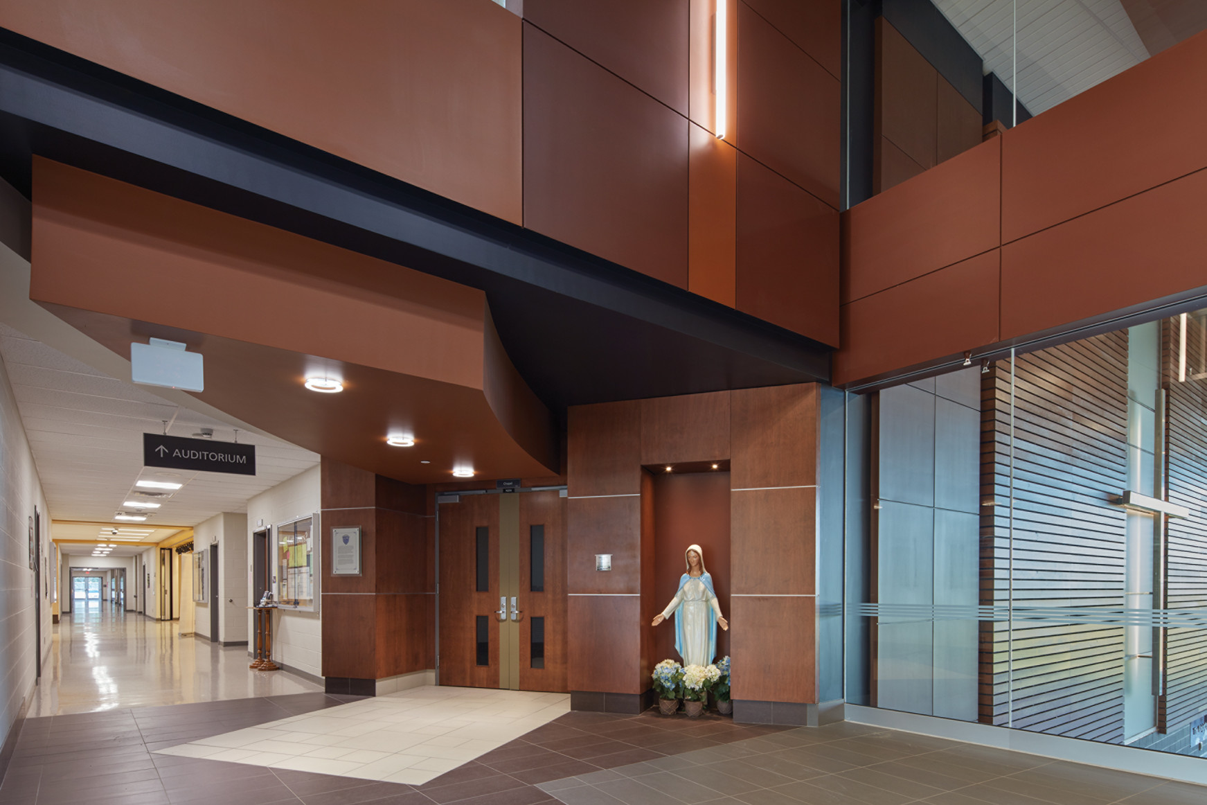 Double height atrium space with statue of the Virgin Mary looking down hallway on left and through wall window to Cafeteria on right