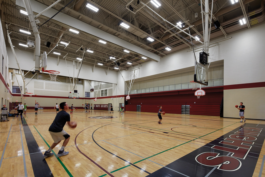 Students playing basketball in gymnasium with black and red Knights logo on floor and exposed white steel beam ceiling