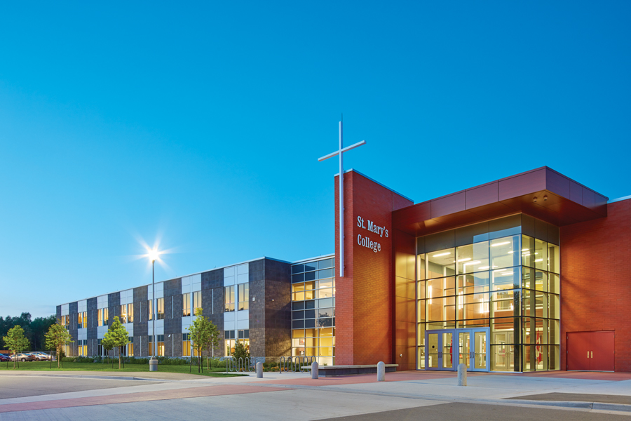 Illuminated façade of two storey school with large cross and glazed double height entrance at dusk