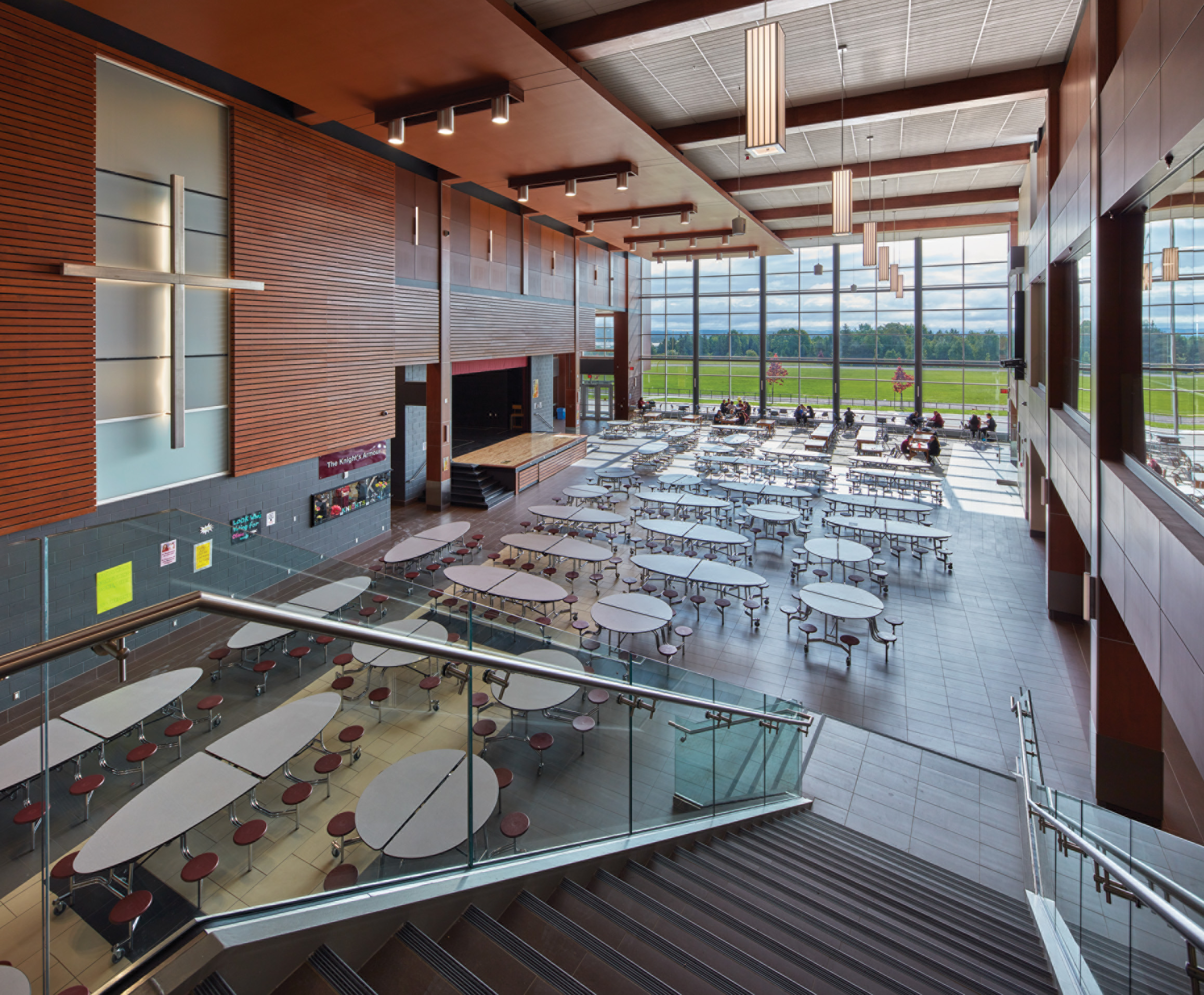 View of Cafeteria from stairs with back lit cross, stage and wood slat wall on left and glazed wall looking out to green field